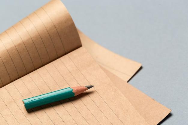 Matita corta indossata con blocco note sulla scrivania grigia Foto Premium