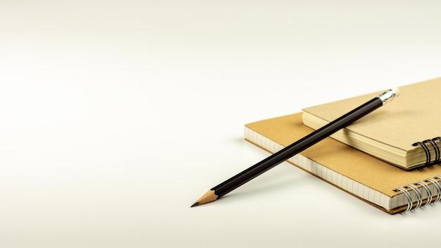 Matita e libro marrone del diario sul fondo bianco dello scrittorio. Foto Premium