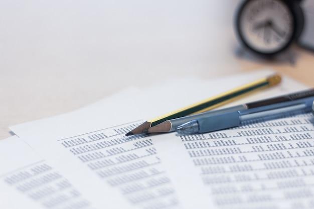Matita e relazione finanziaria sul tavolo con sfondo orologio Foto Premium
