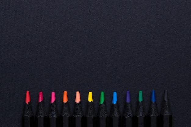 Matite colorate in fila sul nero Foto Premium
