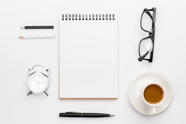 Matite colorate, sveglia, penna, occhiali e blocco note a spirale con tazza di caffè su sfondo bianco Foto Gratuite