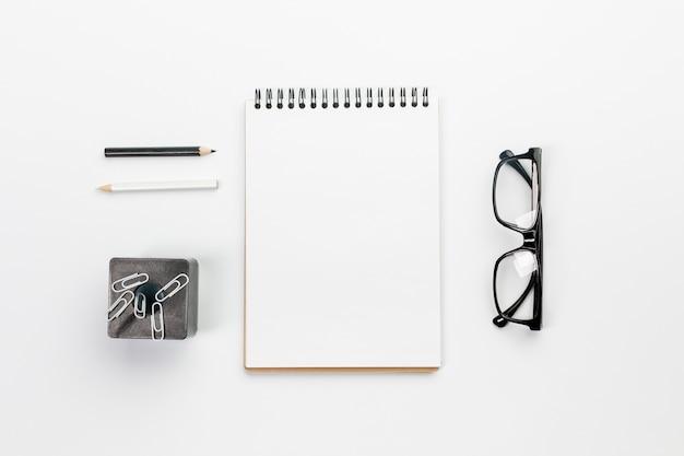 Matite in bianco e nero con notepad vuoto spirale, graffette sul magnete con gli occhiali sulla scrivania Foto Gratuite