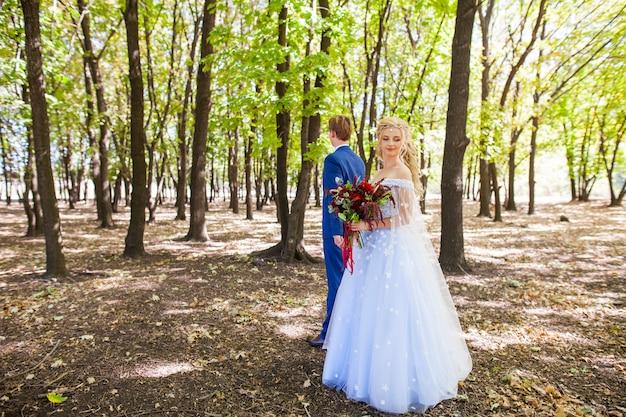 Matrimonio di una giovane coppia con una passeggiata attraverso il parco verde. Foto Premium