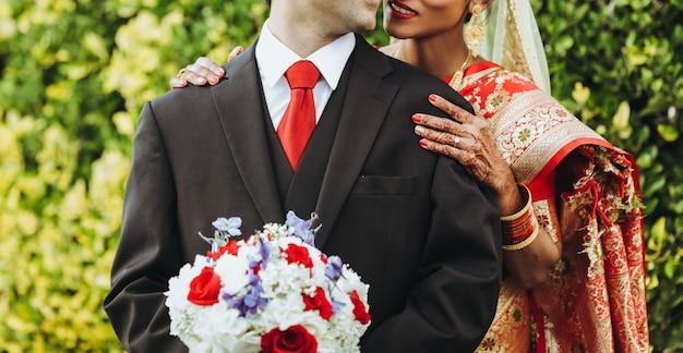 Matrimonio tradizionale indù la sposa abbraccia lo sposo tenero da dietro Foto Gratuite