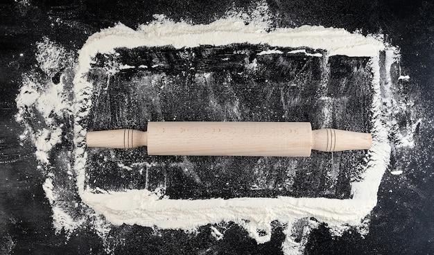 Mattarello di legno su uno sfondo nero, vista dall'alto Foto Premium