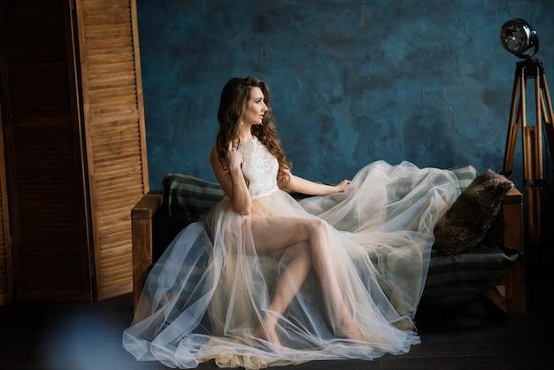 Mattina della sposa ragazza sexy che posa in biancheria intima di pizzo bianco. ritratto di una bellissima giovane femmina in un intimo bianco. donna seducente in lino bianco e vestaglia. Foto Premium
