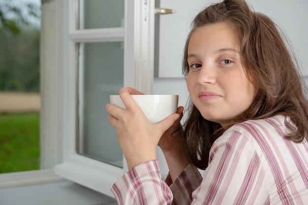 Mattina, ragazza adolescente sta bevendo il caffè in una ciotola Foto Premium