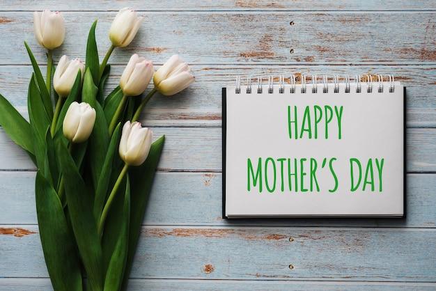 Mazzo dei fiori bianchi dei tulipani con un taccuino con la festa della mamma felice Foto Premium