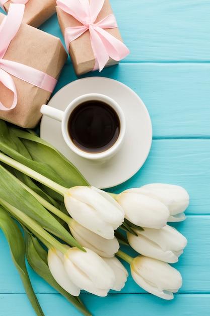 Mazzo dei fiori del tulipano con la tazza di caffè e i regali Foto Gratuite