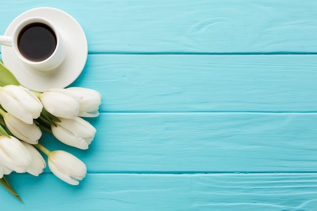 Mazzo dei fiori del tulipano con la tazza di caffè Foto Gratuite