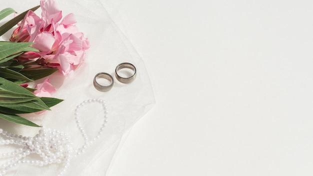 Mazzo dei fiori rosa accanto alla disposizione di nozze con lo spazio della copia Foto Gratuite