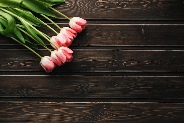 Mazzo dei fiori rosa del tulipano su una tavola di legno Foto Premium
