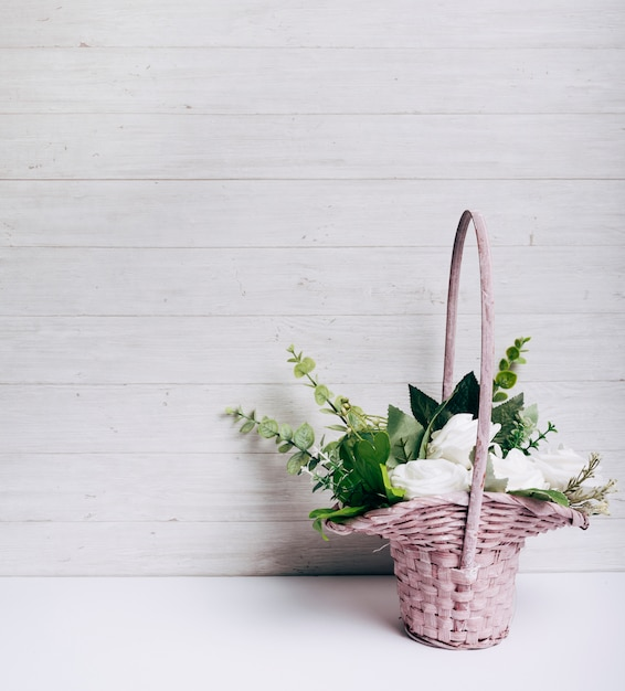 Mazzo del fiore della rosa di bianco sullo scrittorio bianco contro la parete di legno Foto Gratuite