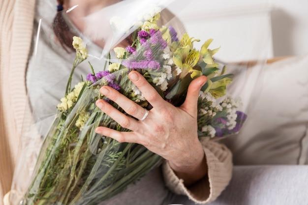 Mazzo della holding della donna del primo piano dei fiori Foto Gratuite