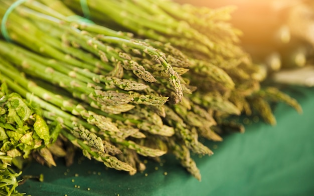 Mazzo di asparagi di giardino crudo sul tavolo in vendita Foto Gratuite