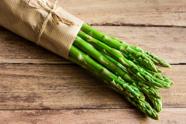 Mazzo di asparago fresco verde legato con spago sdraiato sul tavolo di legno invecchiato tavola Foto Premium
