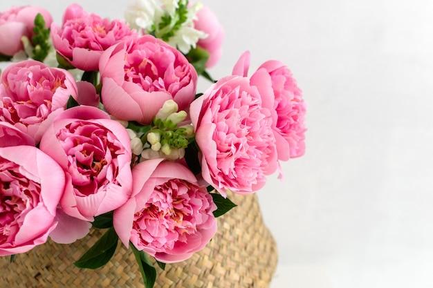 Mazzo di belle peonie rosa nel cestino della paglia Foto Premium