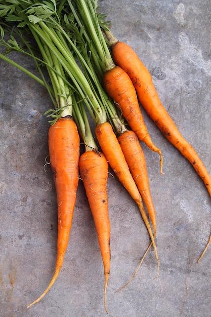 Mazzo di carote su uno sfondo blu in legno Foto Premium