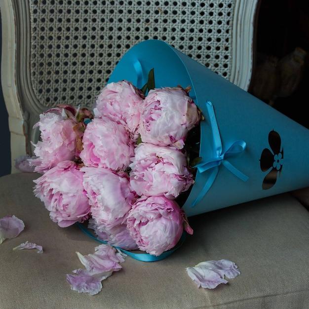Mazzo di cartone blu di peonie rosa su una sedia. Foto Gratuite