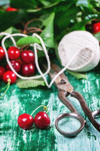 Mazzo di ciliegio con forbici e filo Foto Premium