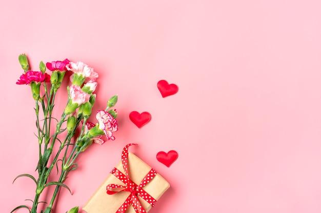Mazzo di diversi fiori di garofano rosa, confezione regalo, cuori su sfondo rosa Foto Premium
