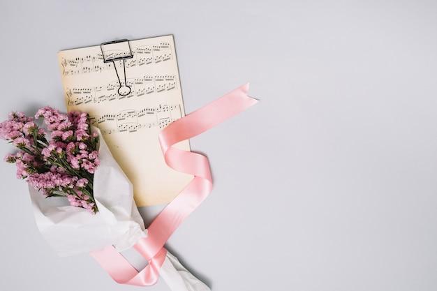 Mazzo di fiori con foglio di musica sul tavolo luminoso Foto Gratuite
