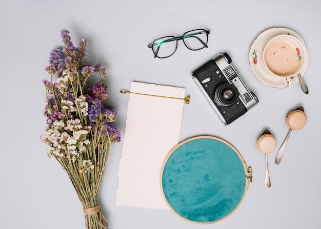 Mazzo di fiori con macchina fotografica e caffè sul tavolo luminoso Foto Gratuite