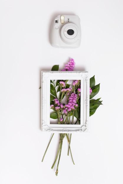 Mazzo di fiori e cornice vicino alla telecamera Foto Gratuite