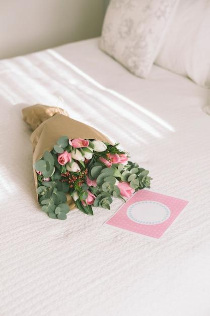 Mazzo di fiori in carta da imballaggio sul letto Foto Gratuite