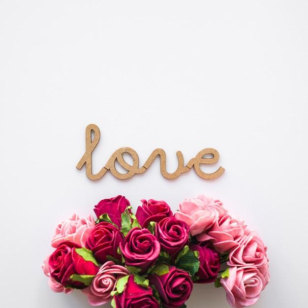Mazzo di fiori vicino alla scrittura d'amore Foto Gratuite