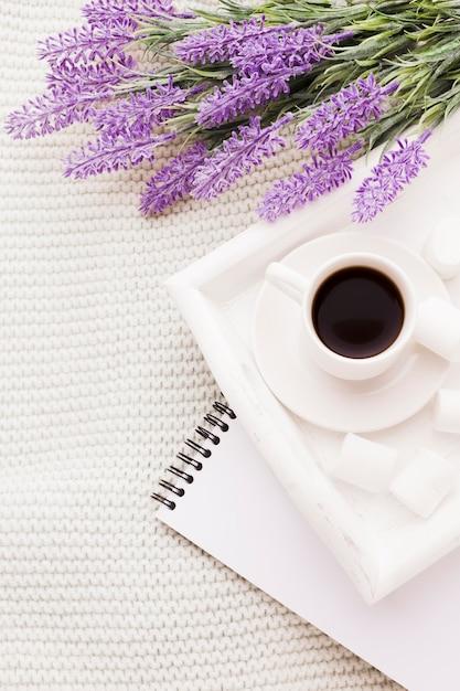 Mazzo di lavanda e tazza di caffè con il taccuino Foto Gratuite