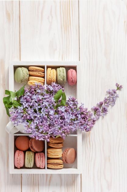 Mazzo di lillà fragrante fresco in tazza bianca e biscotti deliziosi dei maccheroni in scatola Foto Premium