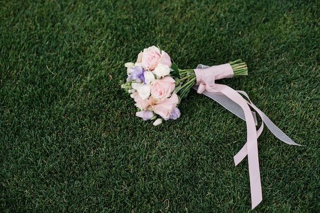 Mazzo di nozze delle rose rosa e bianche che si trovano sull'erba Foto Premium