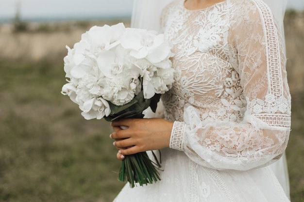 Mazzo di nozze fatto delle peonie bianche nella mano della sposa all'aperto Foto Gratuite