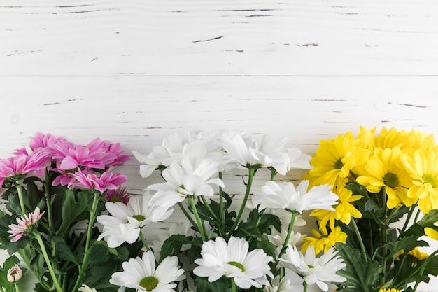 Mazzo di rosa; fiori gialli e bianchi del crisantemo sul contesto strutturato di legno bianco Foto Gratuite