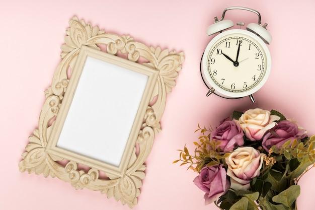 Mazzo di rose accanto a orologio e cornice Foto Gratuite