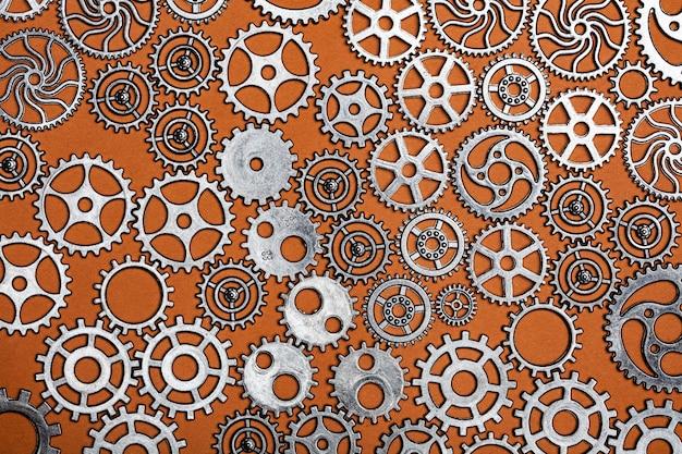 Mazzo di ruote dentate su uno sfondo arancione. Foto Premium