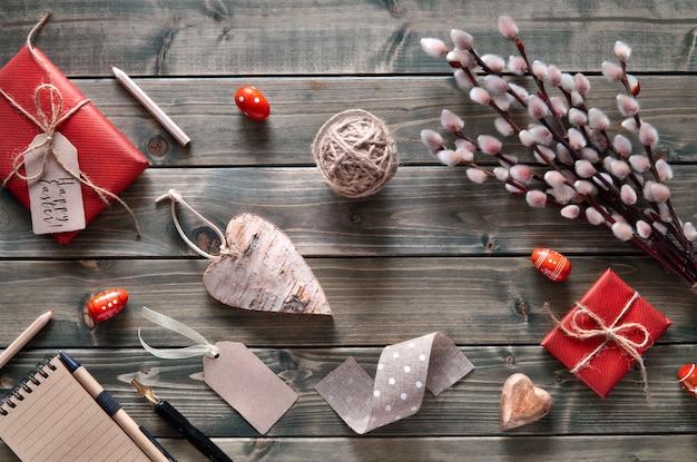 Mazzo di salice, regali avvolti, quaderno e cuore in legno Foto Premium