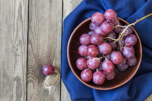 Mazzo di uva rossa sui tessuti blu in una ciotola, su una tavola di legno. copia spazio. stile rustico Foto Premium