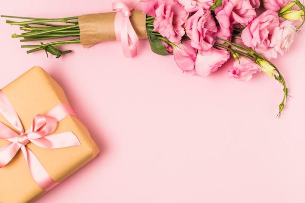 Mazzo e contenitore di regalo freschi rosa del fiore di eustoma contro fondo rosa Foto Gratuite