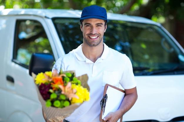 Mazzo ed lavagna per appunti sorridenti del fiore della tenuta del fattorino Foto Premium