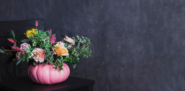 Mazzo floreale di autunno in vaso colorato della zucca sulla sedia nera, sedere Foto Premium