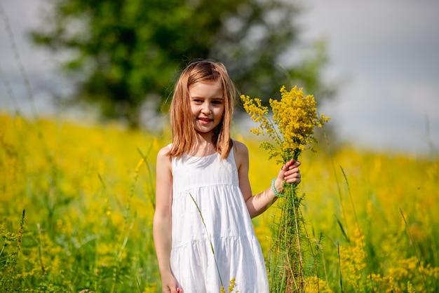 Mazzo sveglio del wildflower della holding della bambina Foto Premium