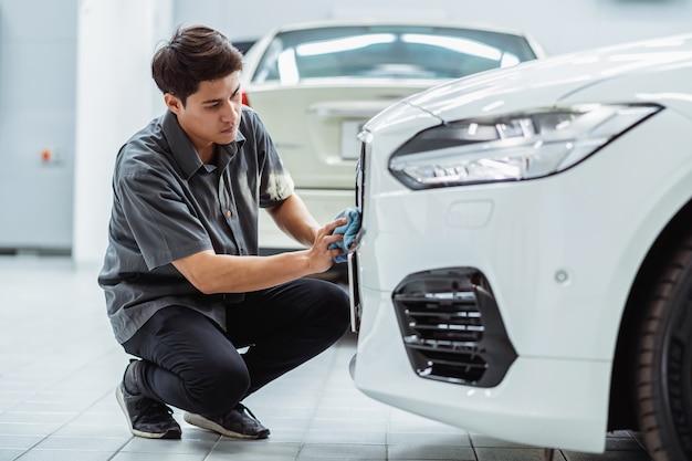 Meccanico asiatico che pulisce l'automobile nel centro di servizio di manutenzione che è una parte dello showroom Foto Premium