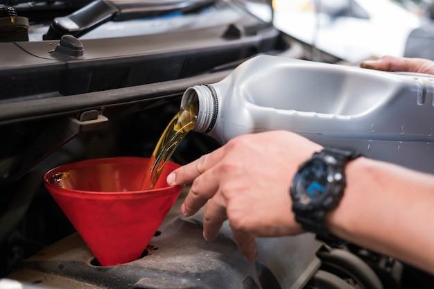 Meccanico che versa olio sul motore del veicolo. Foto Premium