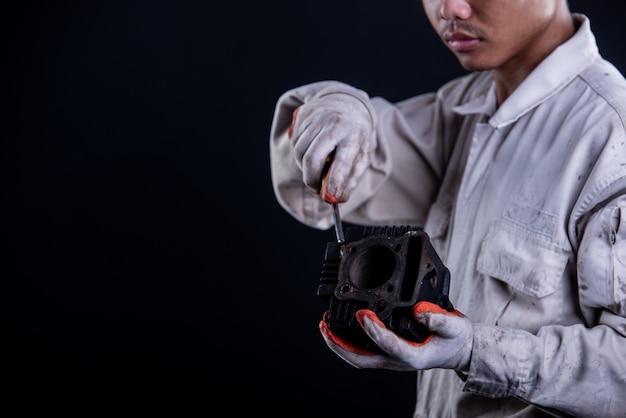 Meccanico di automobile che indossa una chiave della tenuta del supporto dell'uniforme bianca Foto Gratuite