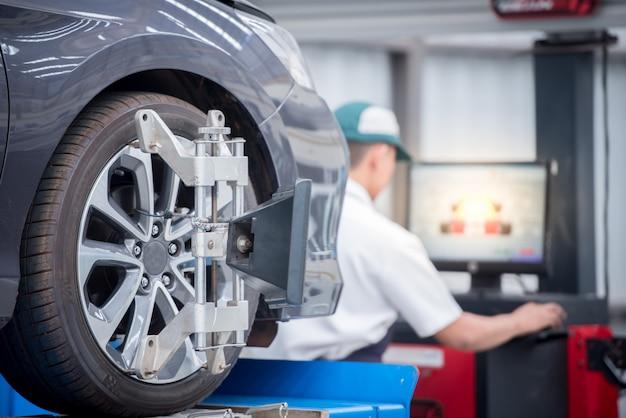 Meccanico di automobile che installa sensore durante la regolazione delle sospensioni. lavori di allineamento delle ruote presso la stazione di servizio di riparazione Foto Premium