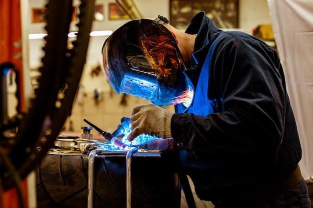 Meccanico di automobile professionista che lavora nel servizio di riparazione automatica sulla tagliatrice del gas dell'argon Foto Premium