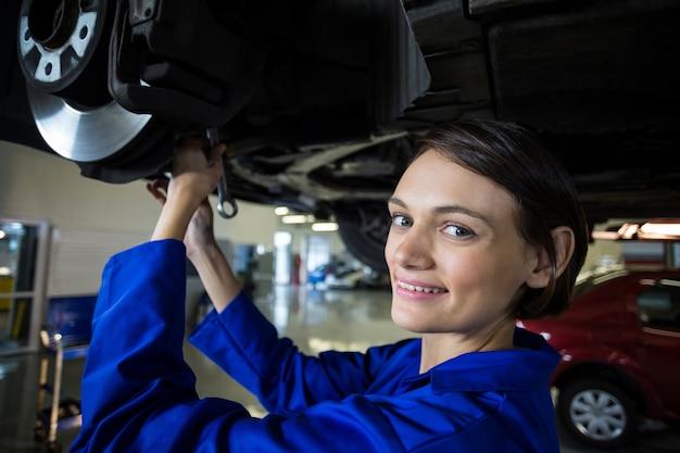Meccanico femminile fissazione di un freno a disco ruota auto Foto Gratuite
