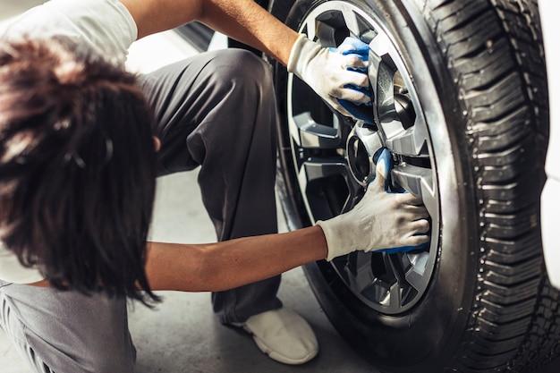 Meccanico maschio dell'angolo alto che controlla la ruota di automobile Foto Gratuite